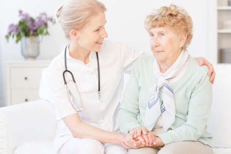 Smiling nurse with stethoscope hugs old lady with white neck scarf during meeting