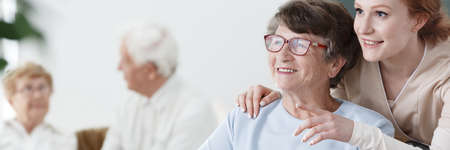 Helpful volunteer taking care of senior lady at healthcare home Stock Photo
