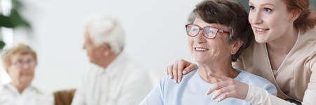 Helpful volunteer taking care of senior lady at healthcare home Standard-Bild