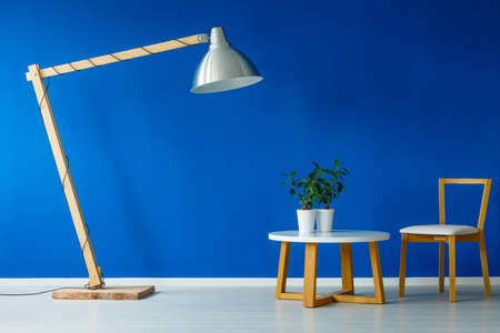modern living room: Giant lamp standing over a small wooden table with two plants and a chair in a scandinavian design day room Stock Photo