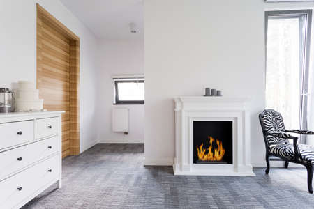 white wood floor: Shot of a full of light room interior with a digital fireplace