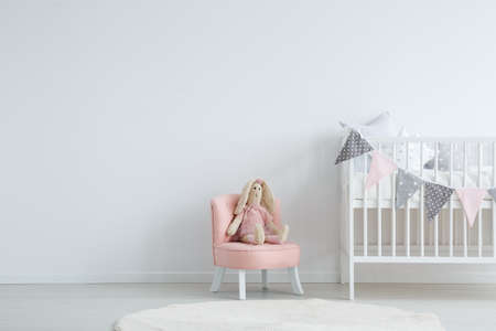 Roomy children's bedroom with a white, circular carpet, a pink chic chair with a toy sitting on it, and a baby bed Stockfoto