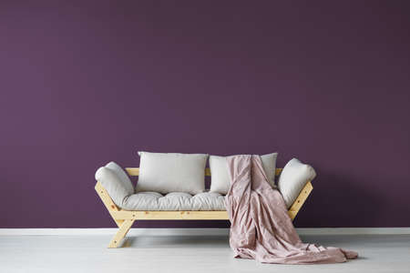 Violet day room interior with a cozy couch and a claret blanket Stok Fotoğraf