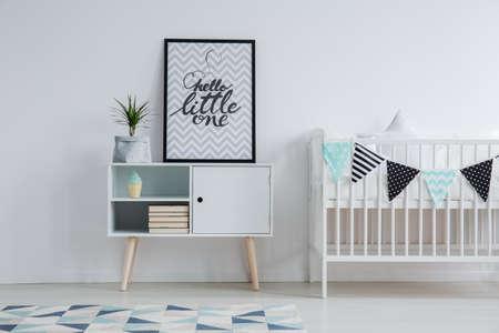 Dormitorio de niño escandinavo moderno interior con una cama pequeña, alfombra monocromática, y un cartel con el texto de pie en un armario al lado de una planta Foto de archivo - 84011019