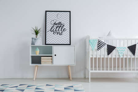 Modern Scandinavian childs bedroom interior with a small bed, monochromatic carpet, and a poster with text standing on a cupboard next to a plant