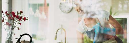 Gelukkige jonge vrouw die willekeurige karweien rond het huis doen Stockfoto