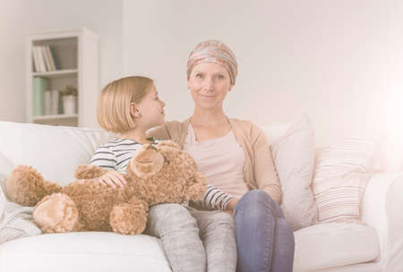 Little caring child supporting sick mother fighting with breast cancer