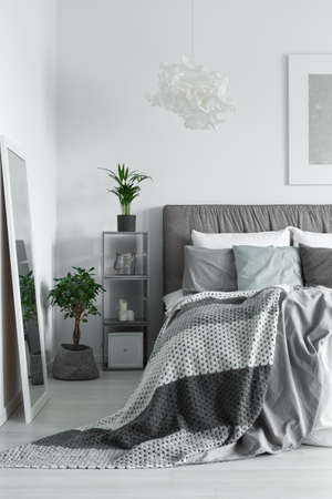 mirror: Blanket with dots falling off the king-size bed in white room