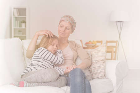 Sick woman suffering from cancer hugging little daughter at home
