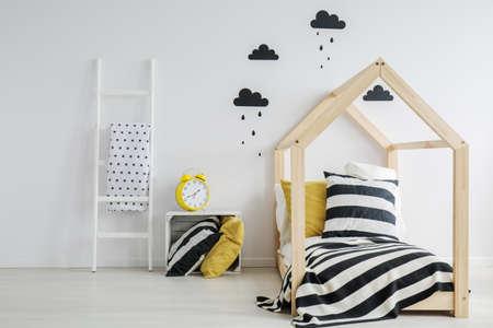 대형 노란색 알람 시계가 달린 세련되고 현대적인 어린이 침실, 벽에 검은 비오는 구름 스티커, 스트라이프 침구가 달린 나무 침대
