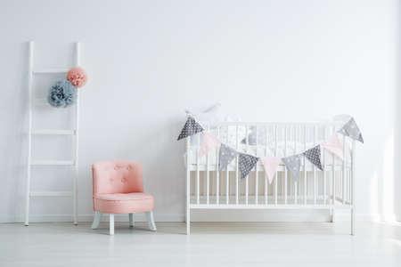 Interiore della stanza del bambino minimalista con una sedia elegante, piccola, elegante, rosa, una scala decorata e un letto per bambini