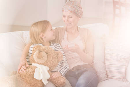 Little girl talking with loving ill mother wearing headscarf Stock Photo