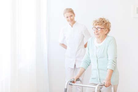 笑顔の看護師が病院に歩いてフレームを使用している年配の女性について世話します。 写真素材