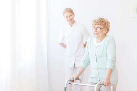 Smiling nurse takes care about senior woman who uses walking frame in hospital Stock Photo