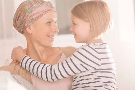 Girl looking with love and care into sick mothers eyes Stock Photo