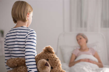 Small daughter holding teddy bear visiting sick mother in hospice