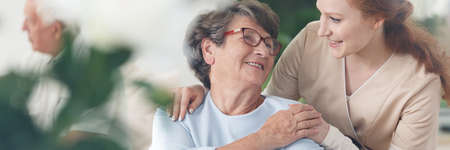 Professional helpful caregiver comforting smiling senior woman at nursing home Stockfoto