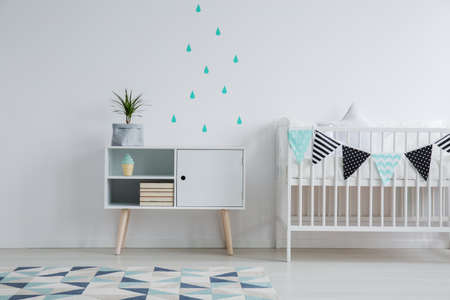 Cozy interior of kids bedroom with a mint water drop stickers on the wall, a plant standing on a cupboard, and a small bed for a baby decorated with washi tape Stock Photo