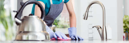 Woman in rubber gloves rubbing the countertop with a pink dishcloth
