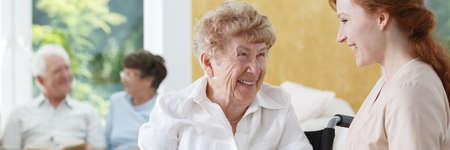 Happy senior woman talking with friendly nurse at geriatric ward Standard-Bild