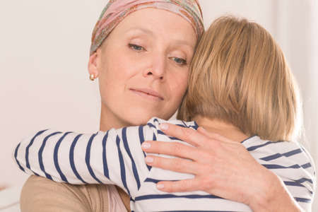 Sick mother with brain tumor tightly hugging her little child Stock Photo