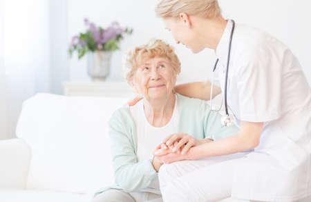 セーターで幸せな高齢女は白いソファに座っていると、医師に感謝
