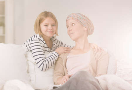 Small girl comforting ill mother in her battle with cancer