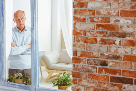 Angry elder man with crossed arms standing by the window