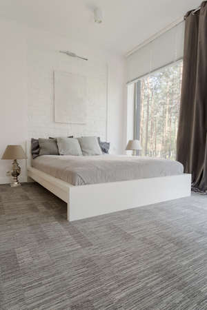 Shot of a spacious and minimalistic bedroom with gray floor and exposed brick on the wall