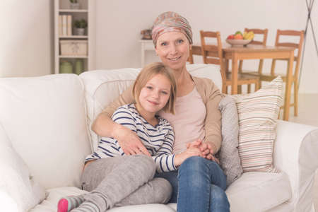 Woman with leukemia wearing headscarf spending time with child daughter Stock Photo