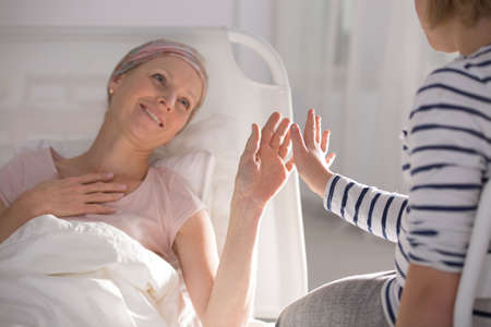 Hopeful cancer woman lying in hospital  playing with daughter