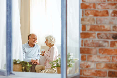 daily life: Happy grandparents sitting on the couch in their apartment talking and smiling Stock Photo