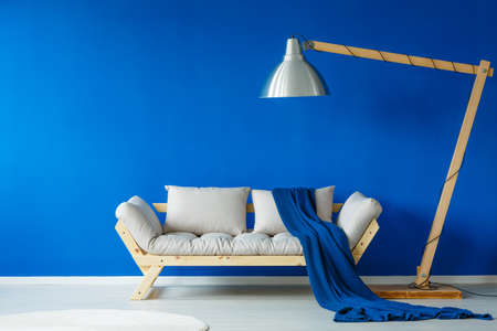 Blue Patterned Blanket Lying On Modern Sofa Next To A Giant Lamp Stock  Photo, Picture And Royalty Free Image. Image 84011181.