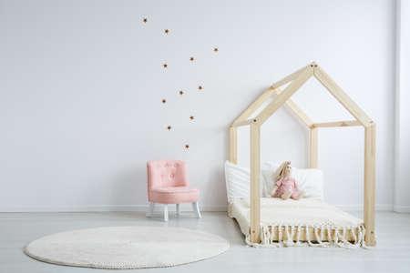 흰 벽에 스타 스티커가 달린 넓은 침실에 현대 어린이 가구, 나무 침대 옆에 파스텔 핑크색의 편안한 세련된 의자 스톡 콘텐츠