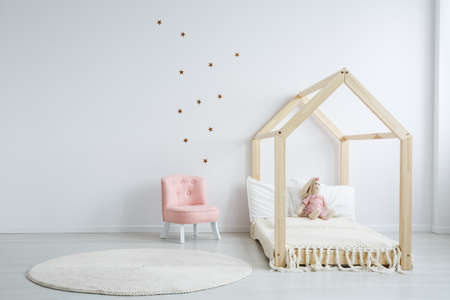 Modern childrens furniture in a spacious bedroom with star stickers on the white wall, and a pastel pink comfortable chic chair next to a wooden bed
