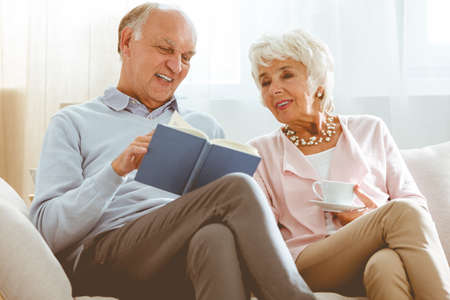 wedding couple: Elder man holding a book and showing illustration to his wife
