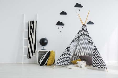 Stylish,patterned teepee with a white teddy bear lying inside it, in a minimalist. scandinavian kid bedroom
