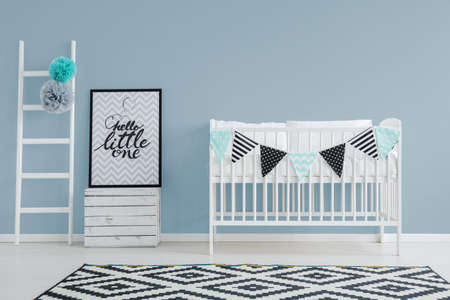 かわいいベッド、装飾が施された、小さなはしごポスターとスタイリッシュなシンプルな赤ちゃんの寝室のインテリア