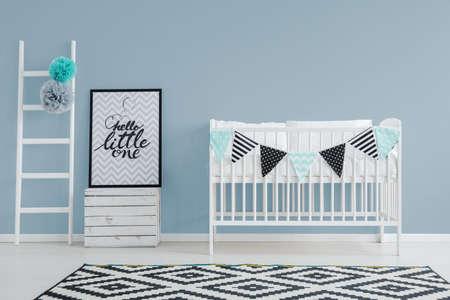 stijlvolle minimalistische baby slaapkamer interieur met een schattig bed, kleine, versierde ladder en een poster Stockfoto
