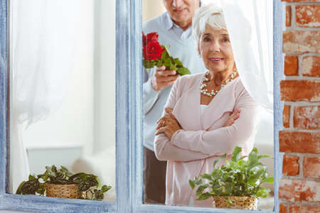 Husband surprising his older wife with pretty red roses