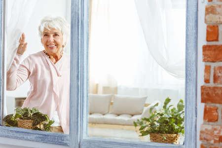 彼女のフラットに立って、窓際の彼女の夫を待っている古い女性 写真素材 - 84011294