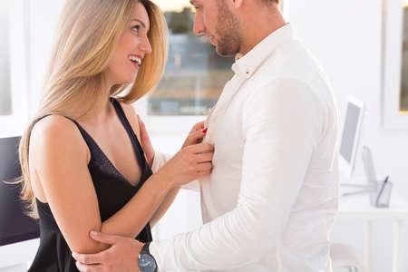 Blond and beautiful woman undressing a man at work Фото со стока