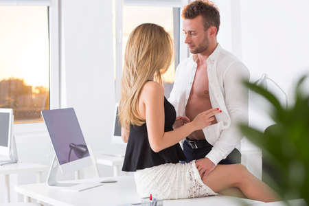Young and beautiful couple having an affair at work