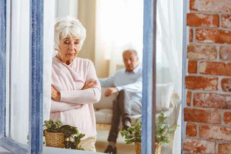 Droevige oudere vrouw die in het raam staat na een argument met haar man