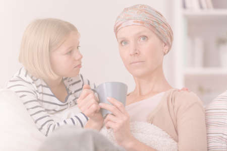 Little girl worrying about tired mother suffering from cancer