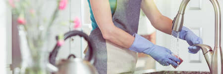 Lady in rubber gloves wetting a sponge over an iron kitchen sink