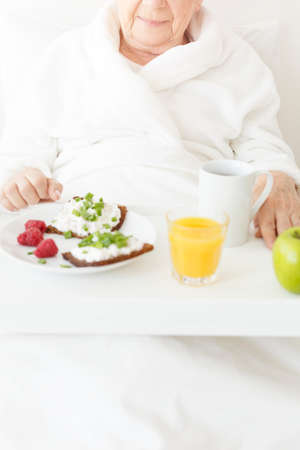Pensioner eats healthy meal at the hospital which consists sandwiches with white curd and juice