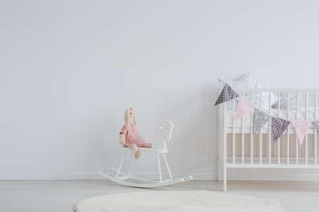 세련 된 scandi 디자인 아이의 침실 장식 된 아기 침대 옆에 락 말에 앉아 박제 동물 토끼와 함께
