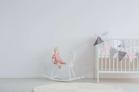 Stylish scandi design kids bedroom with a stuffed animal rabbit sitting on a rocking horse next to a decorated baby bed Banco de Imagens