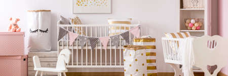 White kid room with crib and pink and golden accents Stock Photo - 84011381